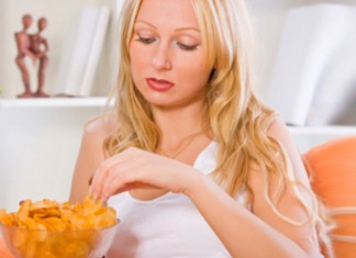 Woman eating chips on the couch