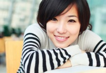 Woman smiling leaning on textbook