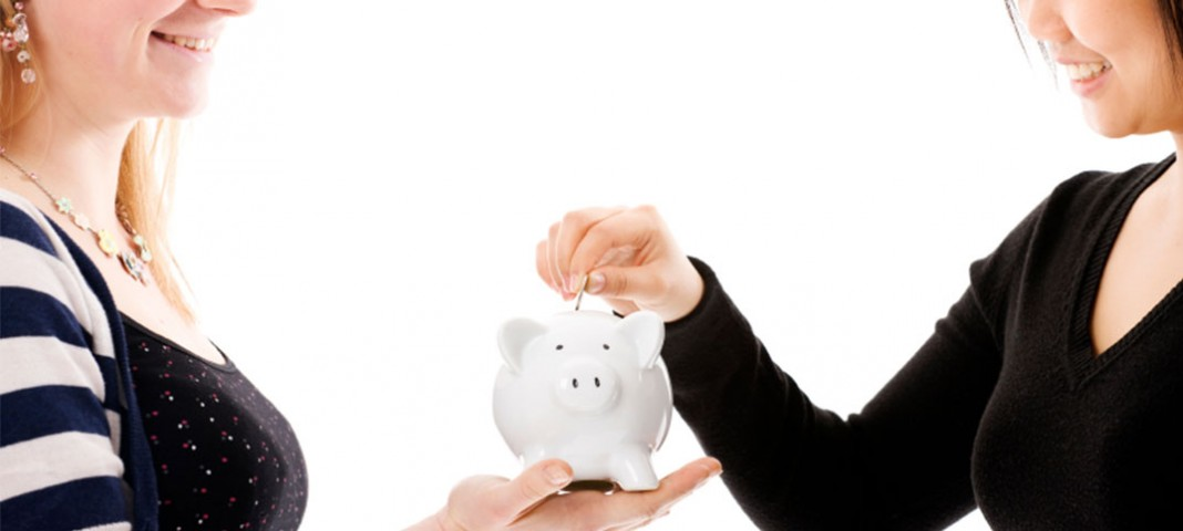 Two women placing money in a piggy bank