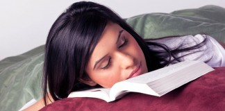 Woman sleeping on textbook