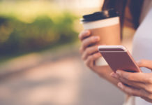 A student holding a coffee and a cellphone