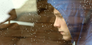 Sad boy looking out a rainy car window