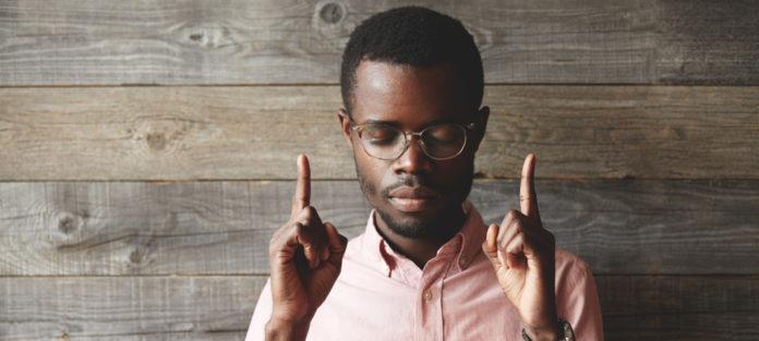A man closing his eyes, pointing upwards