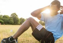 Young man doing crunches on grass