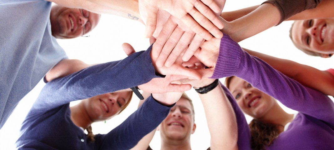 Group of people all putting their hands in the middle