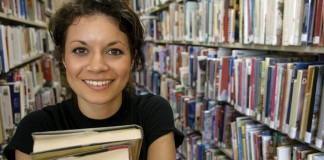 Girl holding books in library