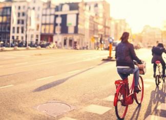 Two people biking in a city street