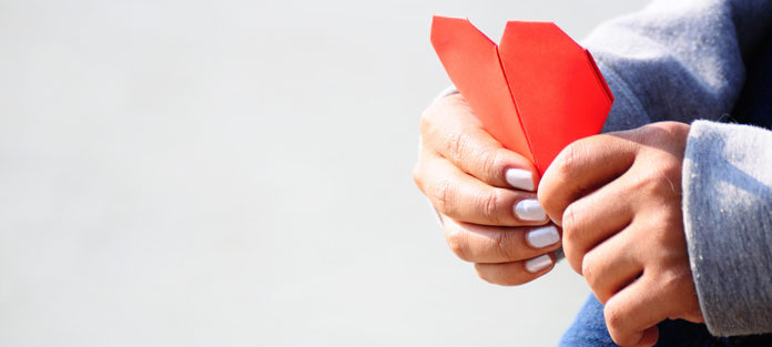 Hands holding paper heart