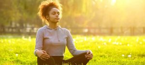 young african american woman meditating in nature with eyes closed