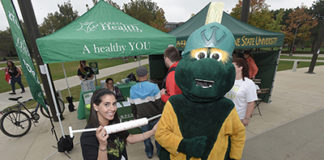 Young woman giving a flu shot to the college mascot