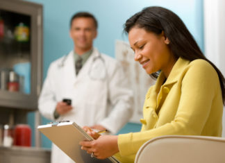 Woman in doctor's office filling out medical form.