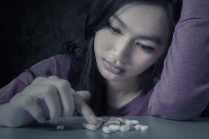 Young woman counting pills