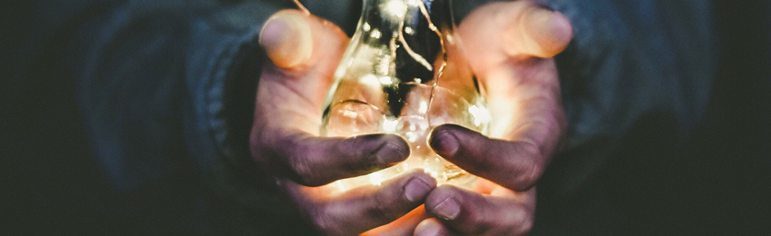 Person's hands holding a lit light bulb in a dark background