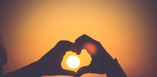 Hands making a heart in the sunset