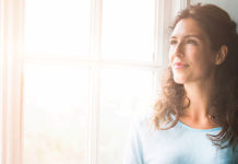 Woman sitting by window looking outside