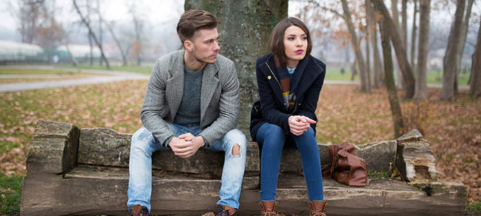 Unhappy couple sitting outside