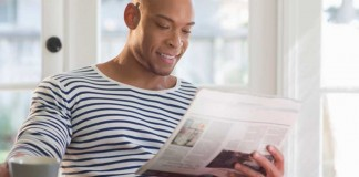 Man drinking coffee and reading the newspaper