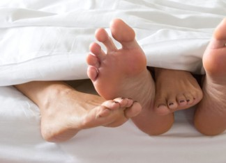 Two pairs of feet under the covers