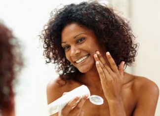 Woman putting lotion on in mirror