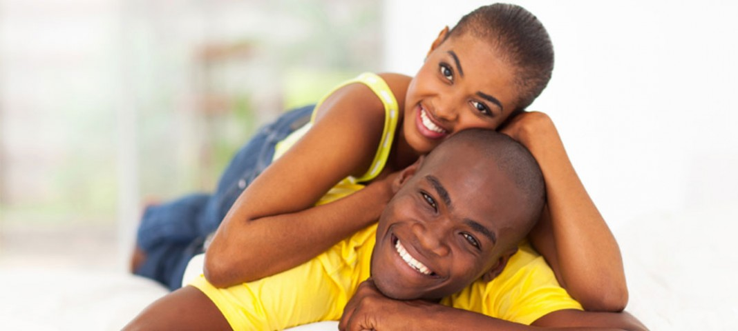 Woman laying on man, both smiling