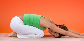 Woman doing yoga in front of orange wall