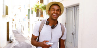 Happy guy listening to music and walking down the street