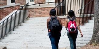 Two girls walking across campus