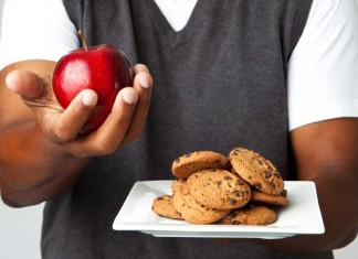 Man holding plate of cookies and apple