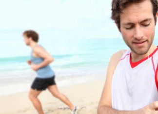 Two men running on beach with smart phones