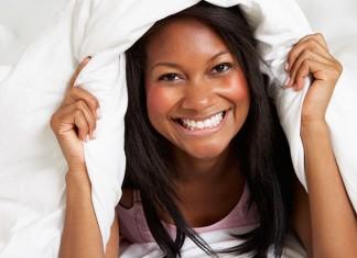 Girl smiling under blanket