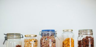 Five mason jars with food inside are lined up in a row on a wooden table.
