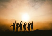 Six people stand with the backs to the camera, silhouetted against an orange sunset.
