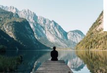 person sitting on a dock at a lake surrounded by mountains
