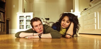 A man and a woman laying on a hardwood floor looking flustered