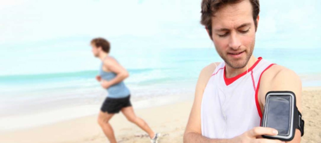Two men running on the beach with smart phones