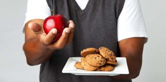 Man holding a plate of cookies and an apple