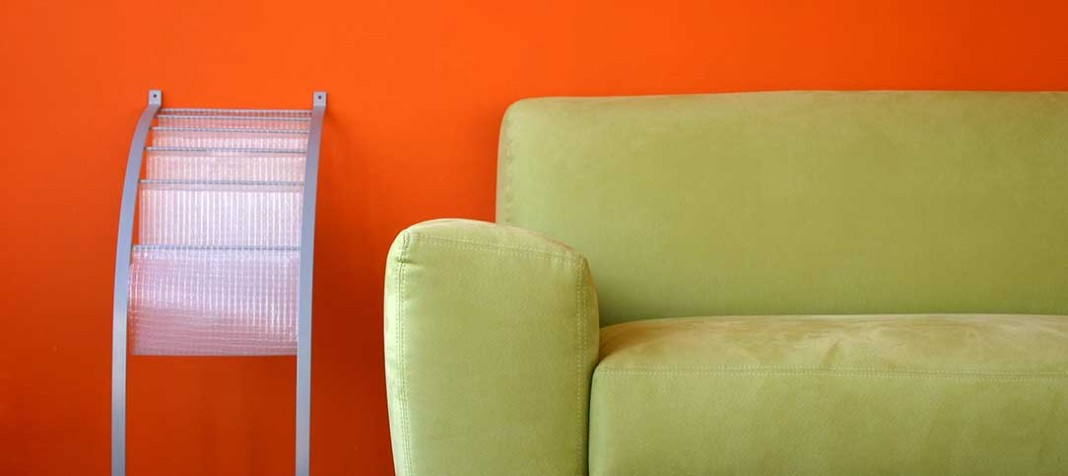 Green couch on orange backdrop