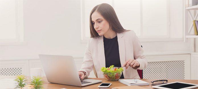 Woman eating a salad at work