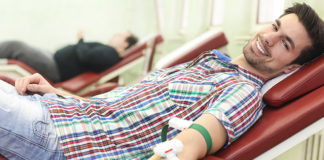 Male college student giving blood
