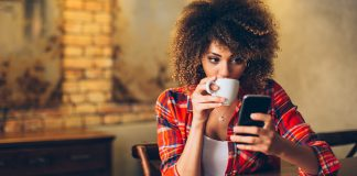 Woman sipping drink from a mug looking at her phone