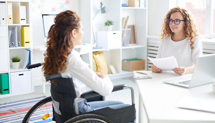 girl in wheelchair talking to teacher