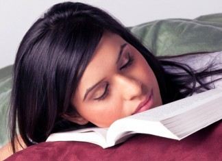 Woman sleeping on textbook
