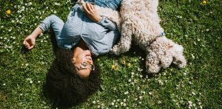 happy girl laying in grass with dog