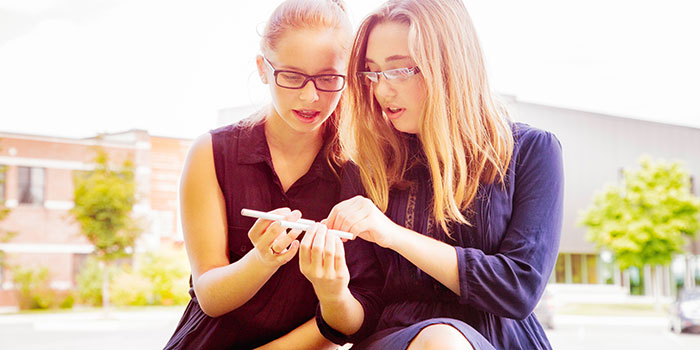 Two girls looking at an e-cigarette