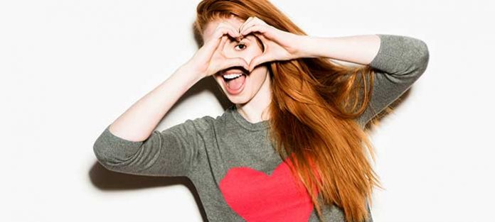 Girl making a heart with hands over her face