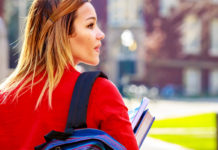 Girl walking outdoors with backpack and books in hand