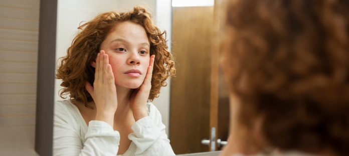 Young woman with freckles looking in mirror