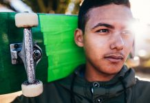 Pensive boy holding skateboard