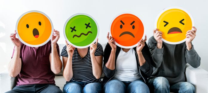 four people holding up emoji faces