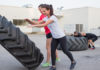 Two girls flipping large truck tire